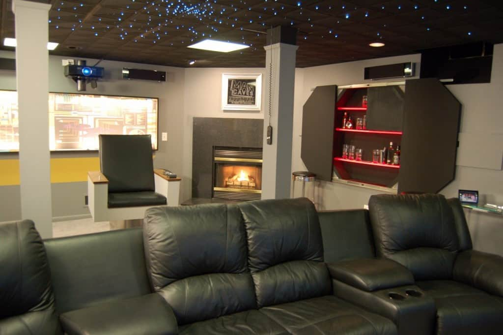 As If Having A Hidden Booze Cabinet With Sliding Doors Screen Projector Fireplace And Those Amazing Seats Weren T Enough This Man Cave Also Boasts